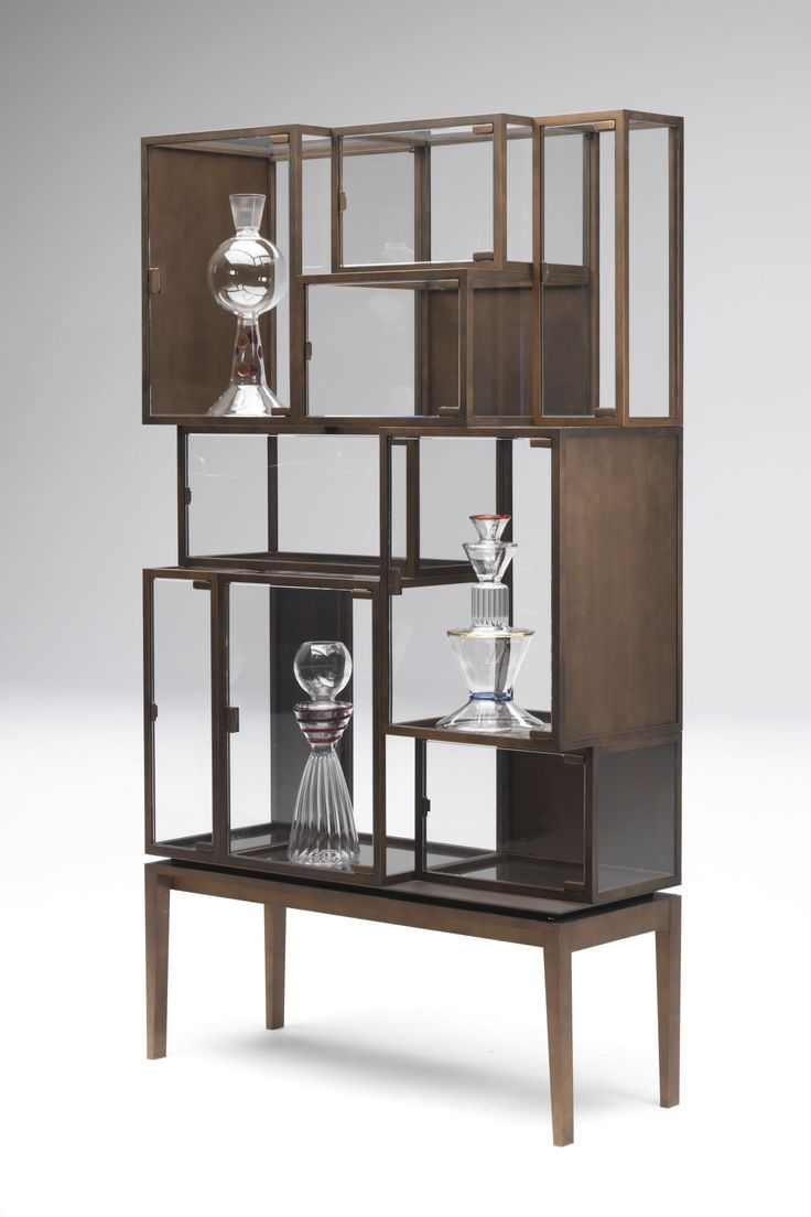 Display case composed of 9 vitrines welded to a metal base. The vitrines are realized with metal profiles that are cut, milled, folded, hand-welded and coated with a burnished copper metallic enamel; the sides of each unit are in 4mm extra clear glass