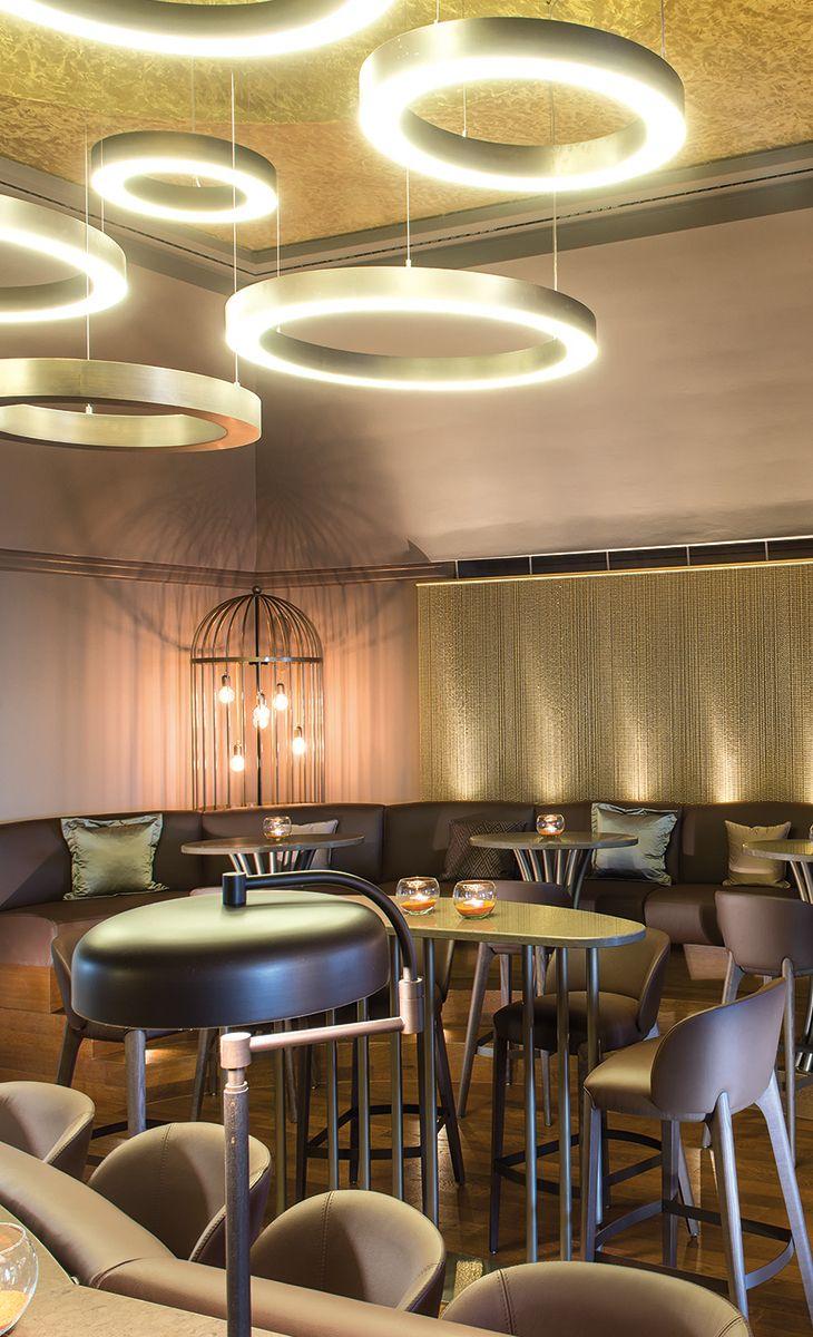 Die Kakadu-Bar im Travel Charme Hotel Kurhaus Binz: Glanzstück des Raumes ist die modernisierte Bar – eine Komposition aus Leder und Messing mit einer gemütlichen Rundecke und eigens designten Lampen in Käfigoptik, um das Thema der Bar aufzugreifen.