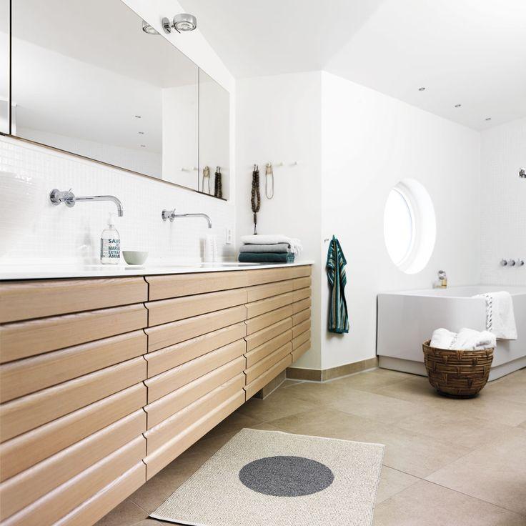 Fra badekarret kan familien nyde udsigten til den norske natur gennem det runde vindue i den funkisinspirerede villa. De funktionelle linjer fortsætter i badeværelsets lange møbel med to håndvaske til en travl familie. Her er alt overflødigt gemt af vejen bag de smukke multifronter i massiv egetræ og i de indbyggede skabe med spejlfront.