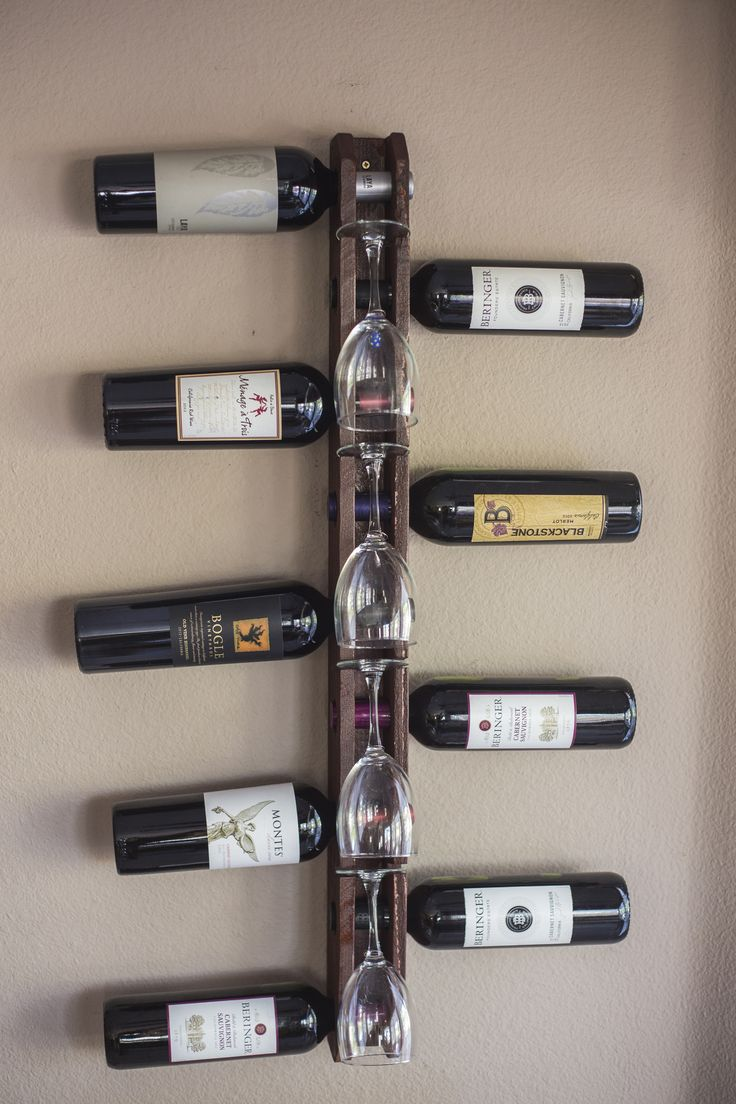 """Wood Wall Mounted Vertical Wine Rack holds 9 bottles.  The wine rack is made of pine, carefully hand crafted in the USA and stained with a warm western red cedar color.  Down the front of the rack are slots to store 4 wine glasses adding an attractive, unique, decorative look to the rack.  Size: 2 1/2 """"x 3 1/2""""x 36""""  Wine rack itself is 2 3/4"""" wide. With bottles it is 21 1/2"""" wide."""