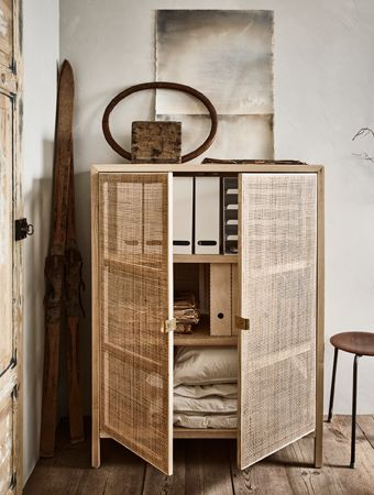 a cabinet holds magazine files paper work and extra bed linens