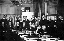 At First Solvay Conference (1911), Curie (seated, 2nd from right) confers with Henri Poincaré. Standing, 4th from right, is Rutherford; 2nd from right, Einstein; far right, Paul Langevin