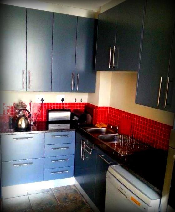 deco kitchen done in flat panel door style. charcoal deco finish. we love the red accesories