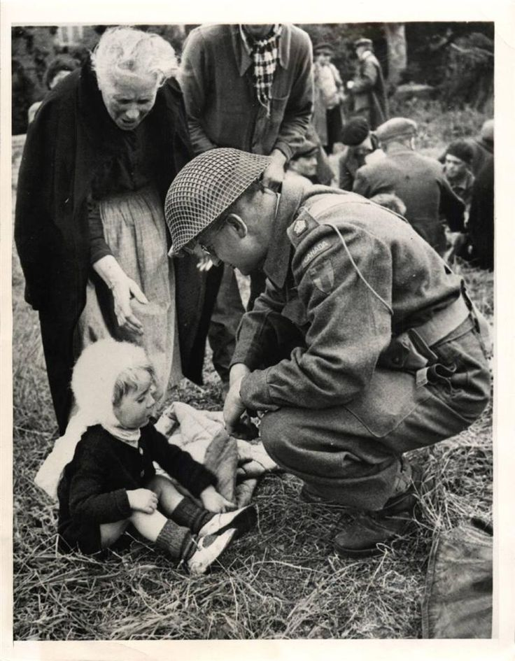 1944- Canadian soldier talks to small refugee boy in the battle area of Normandy, France. The little boy and the old woman behind him were part of a group of Hungarian refugees who had not eaten for three days before they were fed by the Civil Affairs Department of the Allied Forces.