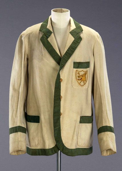 Fashion Museum: Cambridge Wool and silk man's blazer-style cream rowing jacket with green edging and a crest on the chest pocket