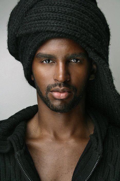 Красивый,  темнокожий мужчина в головном уборе.
