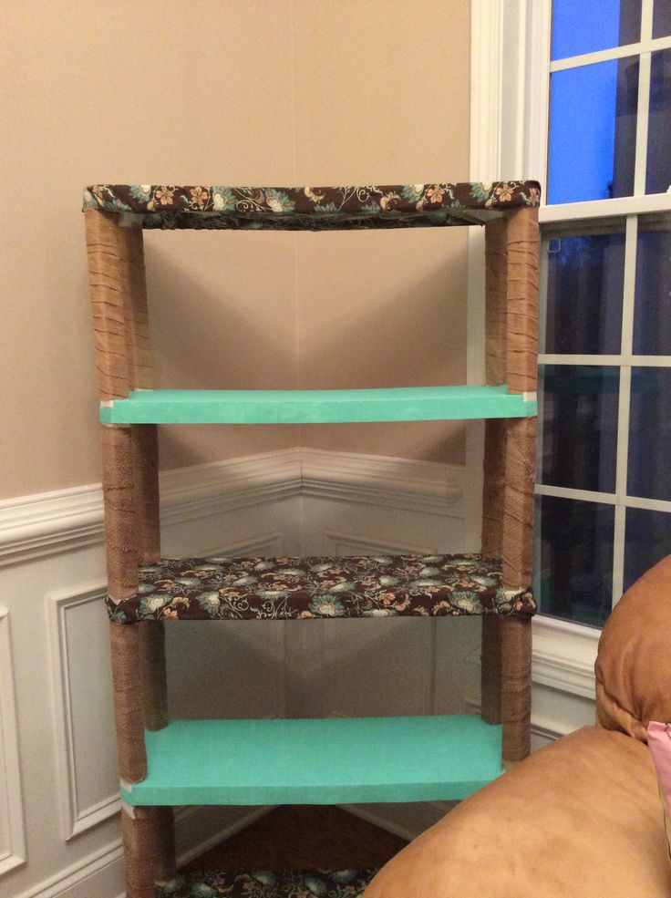 Took an old plastic shelving unit from my garage that was just collecting dust to make this. I painted the 2 shelves and covered the other 2 with fabric. I used burlap to cover the posts.