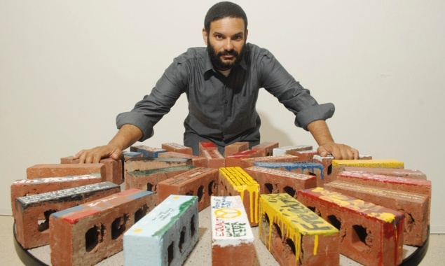 Artist Hatuey Ramos-Fermin with bricks originally sent to Congress to support the building of a wall along the Mexican border now transformed into pro-immigration art installation at Hostos Community College.