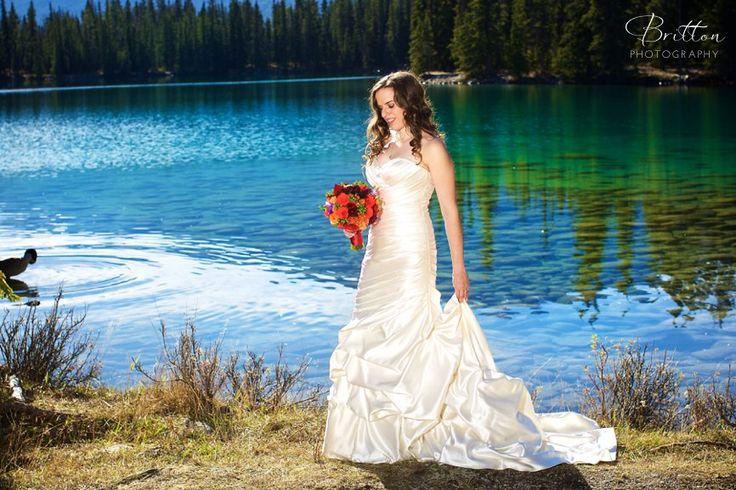 Bride walking along the River in Jasper, Alberta. Photo by Britton Photography.