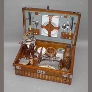 A fine, early and unusual two-person picnic set, by Asprey, London, c1903, the wooden and wicker case with single leather handle to lid and nickelled locks and catches, opening to reveal wooden interior fitted with wicker-handled kettle with ornate burner, stand and oil container, wicker-covered drinks bottle, another glass bottle, Coracle enamel based sandwich box, two stacking glasses in wicker holders, butter jar, two ceramic teacups, .....