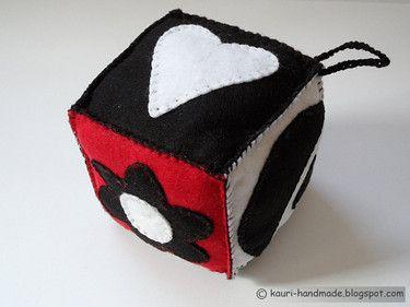 Wykonana ręcznie filcowa kostka dla niemowlaka w kolorach czarno-białym i czerwonym.