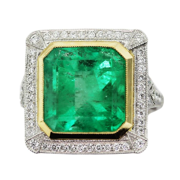 This Vintage Style Platinum and Gold Cocktail Ring features a huge 8.65ct Square Cut Green Emerald measuring 12mm x 11mm. The stone is set in a Platinum and 18k Yellow Gold band.