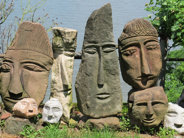 Ted Ludwiczak began carving stone in the late 1980s after retiring. The self taught artist came to carving stone heads while building a stone retaining wall near his house. Seeing a face in a rock he took a hammer and an old lawn mower blade and defined the form. Pleased with the results he felt, one head would look lonely, so he carved other stones heads in the wall.Hundreds of stone heads now make up the environment he refers his Easter Island set on a hillside.Easter Island