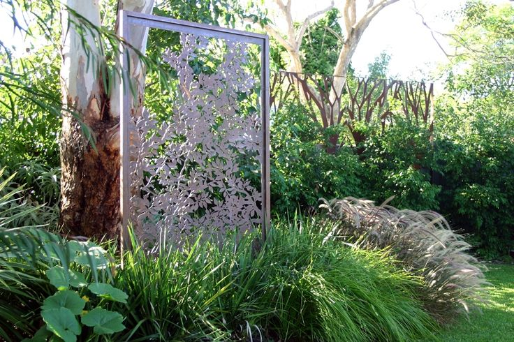 Decorative laser cut 'Banksia' screens in the garden. Rusted metal art with freestanding frame