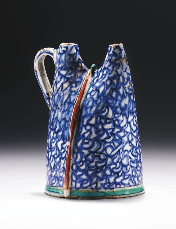 A UNIQUE IZNIK POTTERY WATER FLASK (MATARA), TURKEY, CIRCA 1580-90 of characteristic form with two short tapering spouts and a curved handle, a raised ridge bisecting the body vertically, decorated in underglaze red, cobalt blue and green with an overall marbling pattern