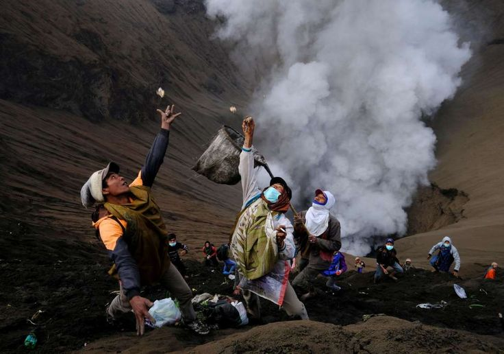 Villagers standing on the slopes near the crater of Mount Bromo try to catch money thrown in by wors... - REUTERS/Beawiharta