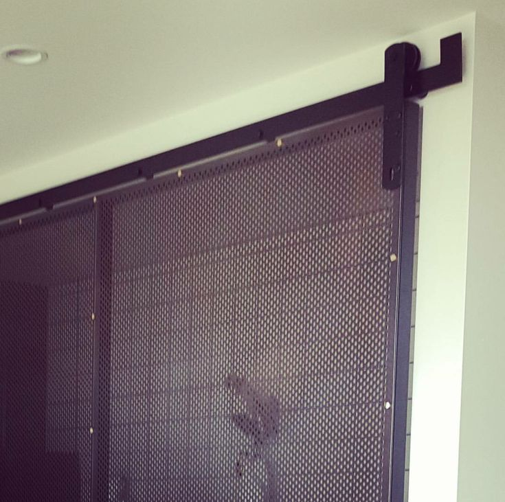 Urban Metal Custom Perf Sliding Screen. We were asked to create an oversized, custom sliding door which fitted the brief of ultra cool meets industrial. Perforated steel panels were hand weathered over a 3 month period before attachment to custom designed frames with brass fittings.Barn  Door fixtures. Sliding doors Decorative screens
