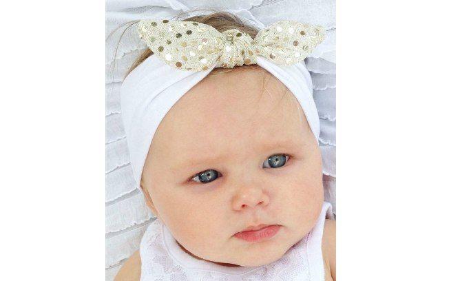 Uma faixa branca que termina em um lacinho dourado é um acessório sofisticado para as bebês. De Etsy. Foto: Pinterest/Katie Campbell