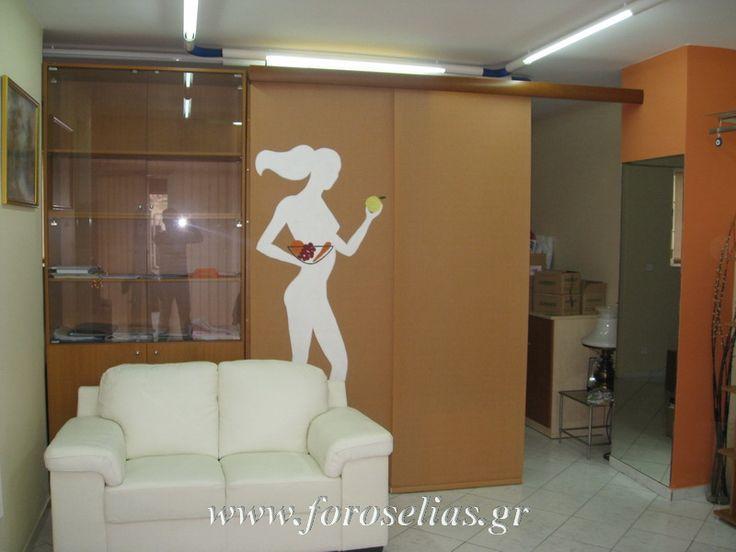 Διατροφολόγος ο πελάτης μας, ήθελε ένα χώρισμα μεταξύ του γραφείου του και του αποθηκευτικού του χώρου. Επιλέξαμε μια φιγούρα που να έχει σχέση με το επάγγελμα του και την ζωγραφίσαμε με το χέρι πάνω σε ένα από τα τρία φύλλα πάνελ. Δείτε το χώρο κι από τις δύο πλευρές στην ιστοσελίδα μας: http://www.foroselias.gr/main.php?ID=6&SUBID=17&SUBSUBID=2&page=2&USERID=967
