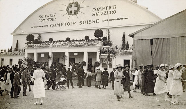 Entrée du Comptoir Suisse 1920 avec la foule qui passe. On ne se lasse pas de remarquer les toilettes d'époque. Eugène Faillettaz, l'initiateur de la manifestation suisse, s'inspire des foires médiévales.