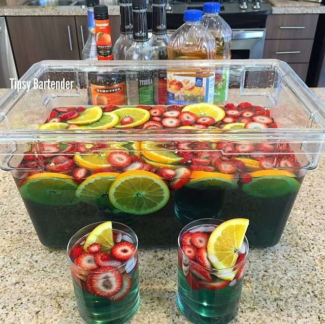 Super Bowl Jungle Juice  Sliced strawberries  Sliced oranges 1 bottle tequila 1 bottle rum 1 bottle vodka 1 bottle peach schnapps 2 bottles white cranberry peach juice 2 bottles white grape peach juice 3/4 of a bottle blue curacao