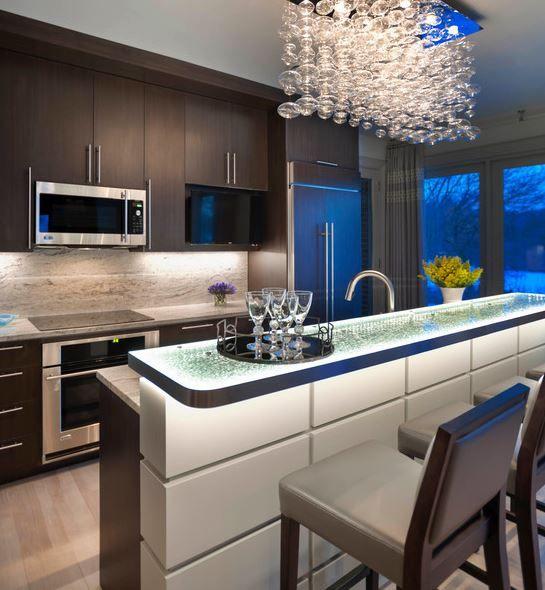 Es una cocina moderna. Hay une guapa araña y hay también une contador.