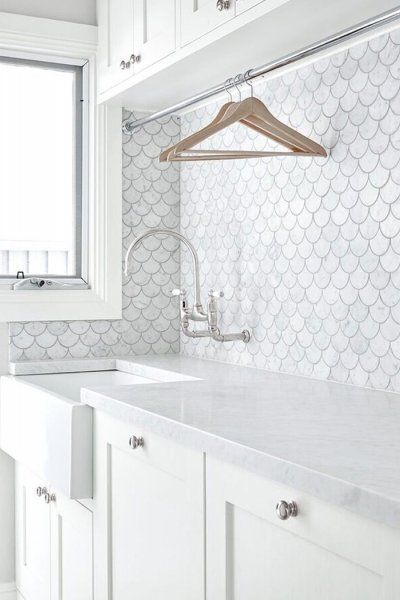 White scalloped tiled laundry room with hanging rack above sink! So pretty and so functional! The English Tapware Company
