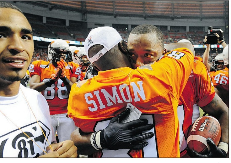 Geroy Simon hugs his dad and his son  looks on after his record-breaking catch, June 29, 2012.