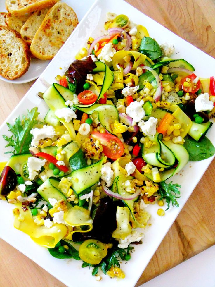myhealthyweighs:  Ribbons of yellow squash and green zucchini take center stage on a bed of mixed greens tossed in a light vinaigrette. The other components are, sliced mini heirloom tomatoes of various colors, red and orange pepper strips, purple onion, peas and grilled corn, ( which I grilled inside) finished off with dots of creamy goat cheese and crunchy hazelnuts and a drizzle more vinaigrette.