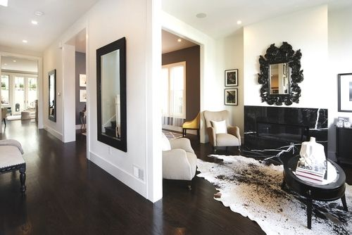 Contemporary open concept living space... love the black and white decor and the mirror repetition in the hallway.