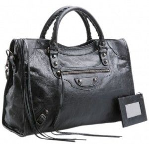 "Black soft lambskin with aged brass hardware, including stud and buckle detail. Tote handles with 4"" drop; removable shoulder strap with 9"" drop. Zip top. Exterior zip pocket. Black cotton-lined inter"