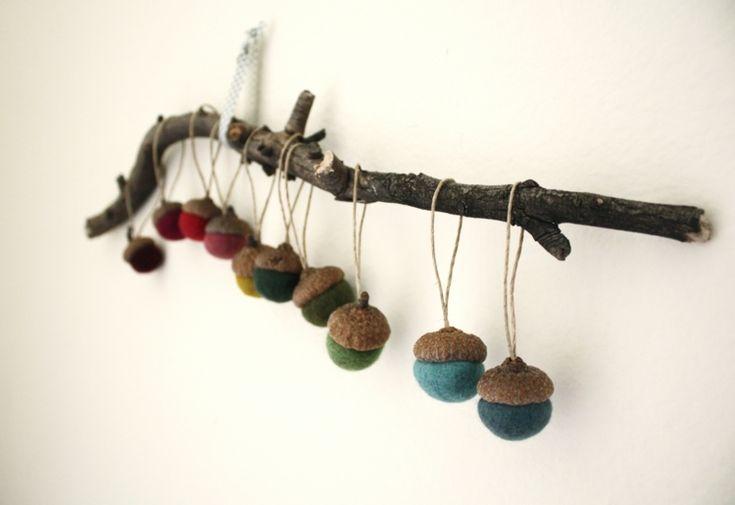 Dekorieren Sie die Wand mit bunt bemalten Eicheln an einem Zweig
