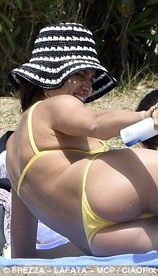 Tan-tastic: Irina ensured she'd be safe in the sun as she lathered herself in lotion on the outing