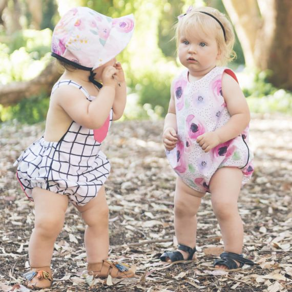 Hand painted blush floral romper with contrasting print panels. Front - blush florals white background. Back - blush florals charcoal background. Plain fuchsia pink pocket. Made from 100% pure kona cotton criss-cross back. Adjustable straps with black wooden button fastenings to suit growing baby. Snap closure at crotch for easy change. Front panel fully lined fuchsia pink cotton. Hand Made in Australia - composition - 100% pure cotton care instructions - cold gentle wash with similar…