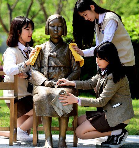 여고생들이 수원에 세워진 '평화의 소녀상'을 정성스럽게 닦고 있습니다. 이 소녀상은 일본군 위안부 피해자를 기리자는 의미로 시민의 성금으로 마련되었다고 합니다.