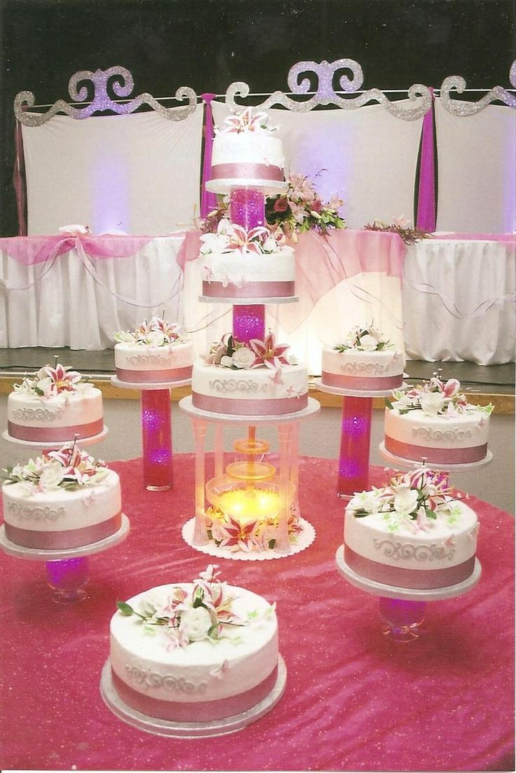 Alexis La Quinceanera cake - Tiered white and chocolate Tres Leches cakes filled with a vanilla mousse displayed on glass vases filled with pink water beads, led lighting and handmade gum paste flowers.