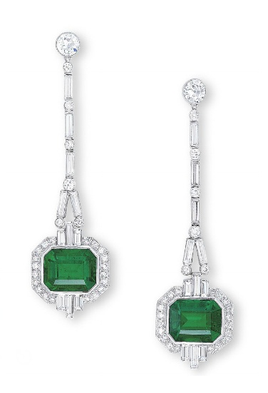 A PAIR OF EMERALD AND DIAMOND EAR PENDANTS   Of geometric design, each suspending a rectangular-shaped emerald weighing 5.08 and 4.80 carats, within a pierced diamond-set surround, accented by baguette-cut diamonds extending to the line of baguette-cut diamonds interspersed by old European-cut diamonds, mounted in platinum, 6.3 cm long