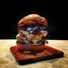 Burger bovino 180g, queijo gruyere e mozzarella, tiras de bacon caramelizado, rodela de abacaxi grelhado com canela, rúcula, aioli de iogurte e mel e pão de batata.