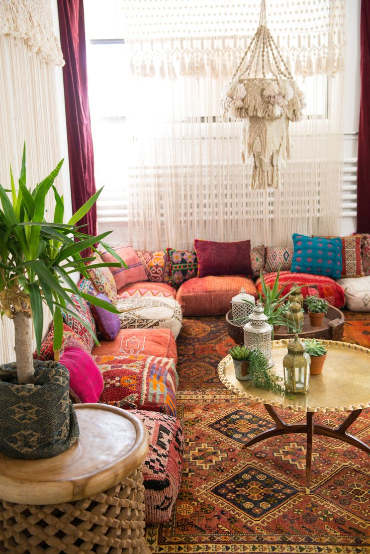 Moroccan floor pillows lined up against a corner w…