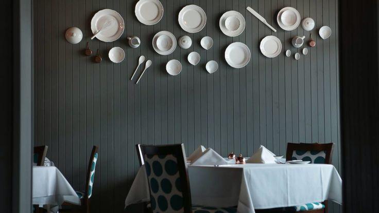 Nest Emporium Interiors. Restaurant interior. Plate wall. Dark walls.