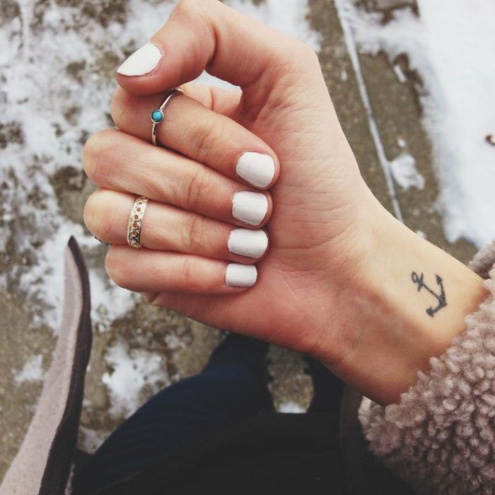 Brazo de una chica con las uñas pintadas de blanco y anillos, mostrando su tatuaje en forma de ancla que está en su muñeca
