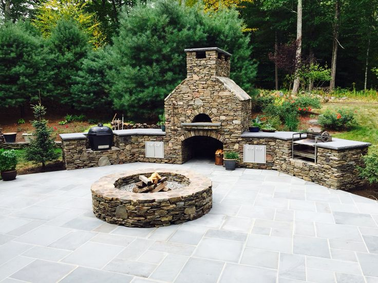 Outdoor Kitchen with pizza oven, fire pit, smoker and rotisserie.