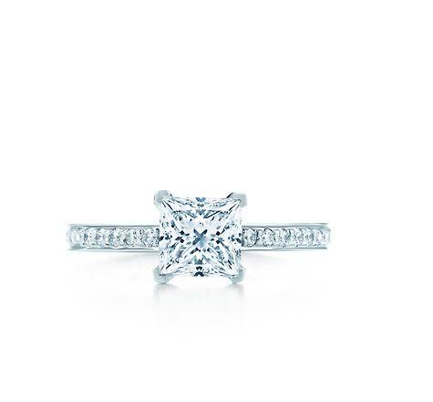 TIFFANY GRACE - platinum band with round brilliant diamonds surrounding a princess-cut diamond.