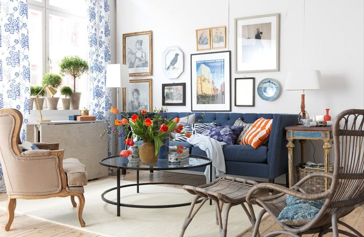 Swedish blue and white room with small touches of orange, and modern pieces that mix well with the vintage furniture. The curtains have embroidered blue on white flowers.