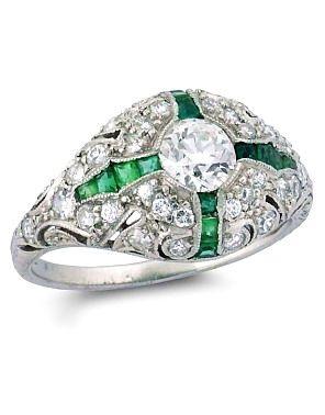 Art Deco diamond and emerald bombé cluster ring, the central brilliant-cut diamond set within a calibré-cut emerald cruciform motif, mounted in platinum