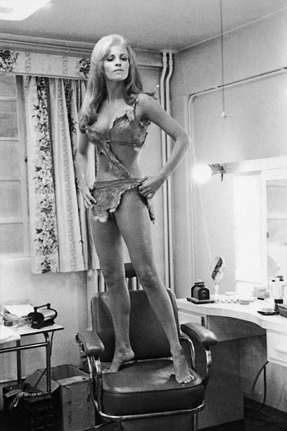American actress Raquel Welch stands on a chair in her in her dressing room during filming of Don Chaffey's prehistoric epic 'One Million Years BC'...