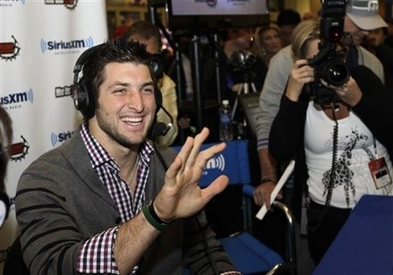 Tim Tebow waves to actress Jenny McCarthy during an interview with Sirius XM radio on radio row at the Super Bowl XLVI media center Friday, Feb. 3, 2012