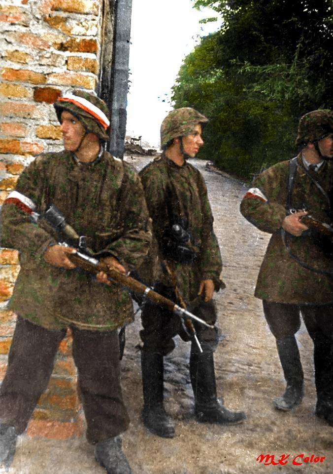 """Patrol z II plutonu """"Alek"""" 2 kompanii """"Rudy"""" Batalionu """"Zośka"""" 5 sierpnia 1944 w wyzwolonym obozie koncentracyjnym na Gęsiówce. Od lewej stoją: Wojciech Omyła """"Wojtek"""", Juliusz Bogdan Deczkowski """"Laudański"""" i Tadeusz Milewski """"Ćwik"""". Kilka minut po tym, jak to zdjęcie zostało zrobione niemiecki pocisk uderzył w ścianę nad ich głowami.Wojtek i Ćwik zginęli jeszcze tego samego dnia od pocisku artyleryjskiego."""