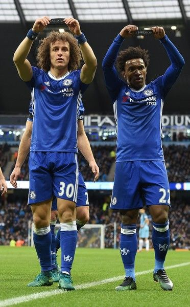 Chelsea's Brazilian midfielder Willian (R) and Chelsea's Brazilian defender David Luiz hold up their black armbands as they celebrate Willian scoring his team's second goal during the English Premier League football match between Manchester City and Chelsea at the Etihad Stadium in Manchester, north west England, on December 3, 2016.  / AFP / Paul ELLIS / RESTRICTED TO EDITORIAL USE. No use with unauthorized audio, video, data, fixture lists, club/league logos or 'live' services. Online…