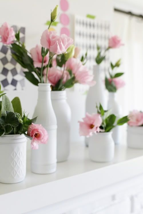 looks like a matte white spray painted  bottles and mason jars. Love the baby pink roses with dark green leaves.